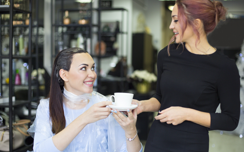 Photo of hairstylist giving her client a cup of coffee