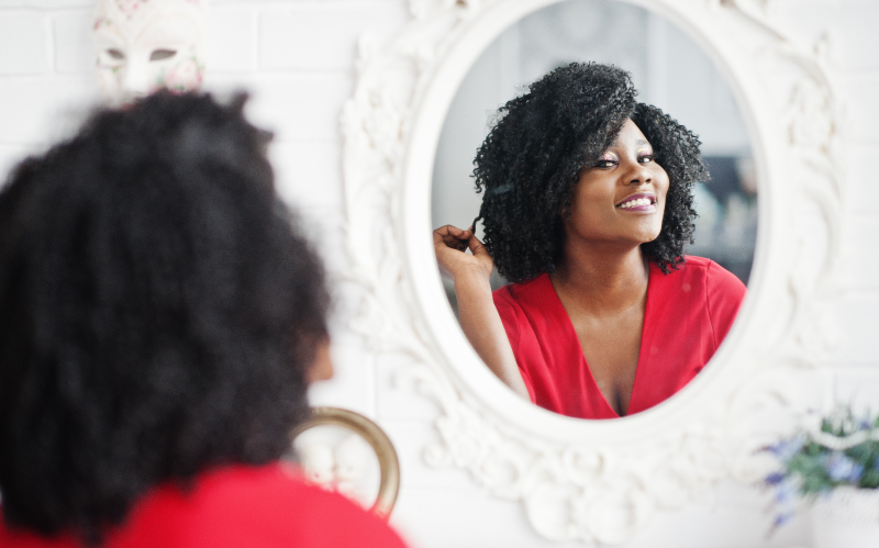 Photo of woman looking in the mirror at her hair